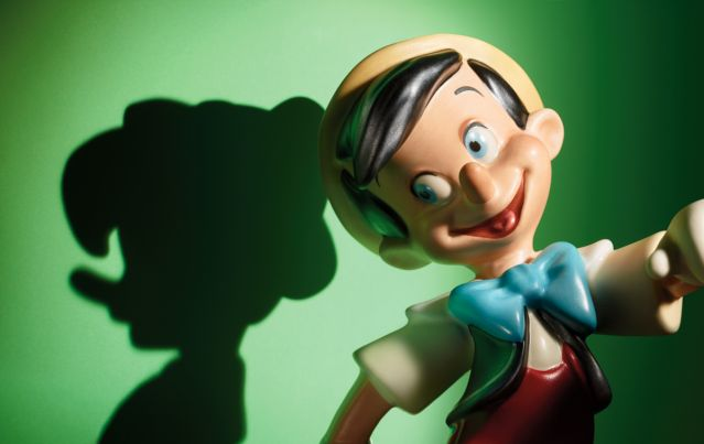 Pinocchio figurine casting shadow of nose growing on wall behind