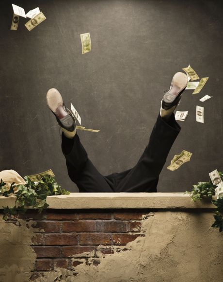 Businessman falling off ledge with money